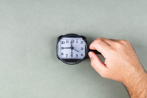 O relógio está correndo e o conceito de gerenciamento de tempo com o relógio na vista superior do plano de fundo cinza. mãos segurando uma lupa. imagem horizontal