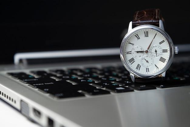 O relógio está no teclado do laptop, o início do dia de trabalho
