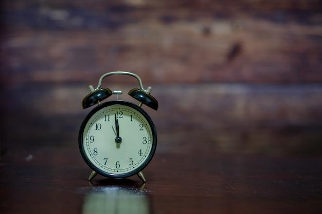 O relógio preto na madeira.