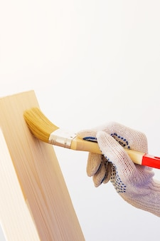 O reparador, carpinteiro, trabalhador duro aplica o verniz protetor com uma escova em uma placa de madeira.