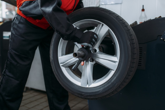 O reparador coloca a roda na máquina de balanceamento, serviço de pneus. homem conserta pneu do carro na garagem, automóvel no macaco, inspeção na oficina