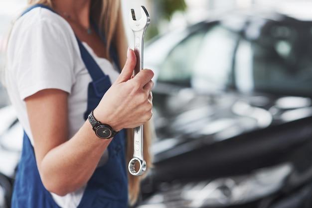 O reparador de bela mulher loira está no trabalho dela. loja de automóveis dentro de casa