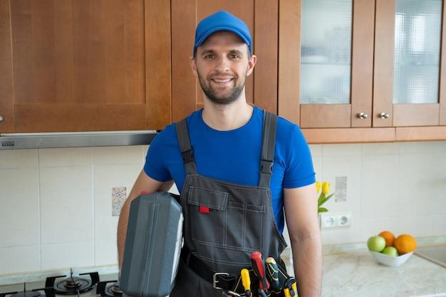 O reparador está na cozinha com um boné azul e escreve em um tablet