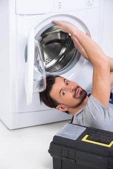 O reparador está reparando uma máquina de lavar.
