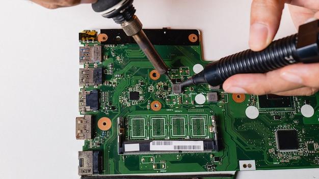O reparador está usando ferro de solda e sugador de chumbo para consertar a placa-mãe.