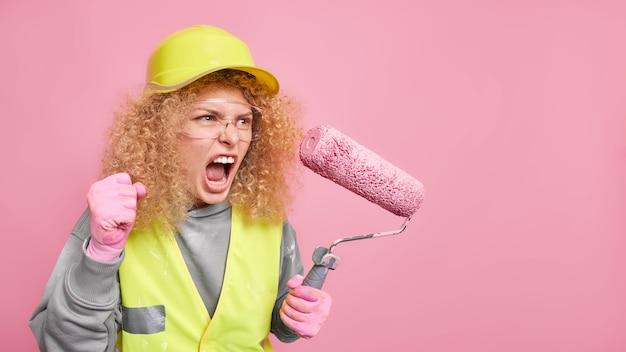 O reparador feminino furioso indignado aperta o punho com aborrecimento grita em voz alta para alguém que faz o reparo feito à mão e a reforma mantém o rolo de pintura ocupado fazendo a reconstrução geral da casa.