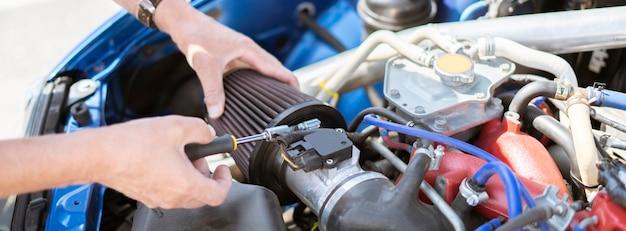 O reparador trabalha com o carro substituindo o filtro de ar de admissão do cilindro