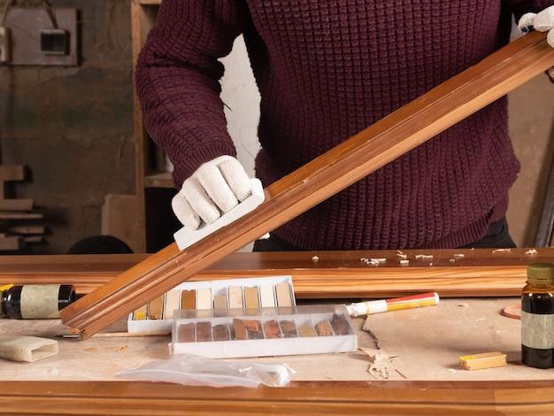 O restaurador restaura uma porta de madeira