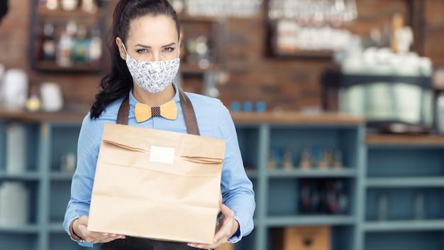 O restaurante é forçado a uma operação limitada, entregando apenas refeições para viagem embaladas em sacos de papel.