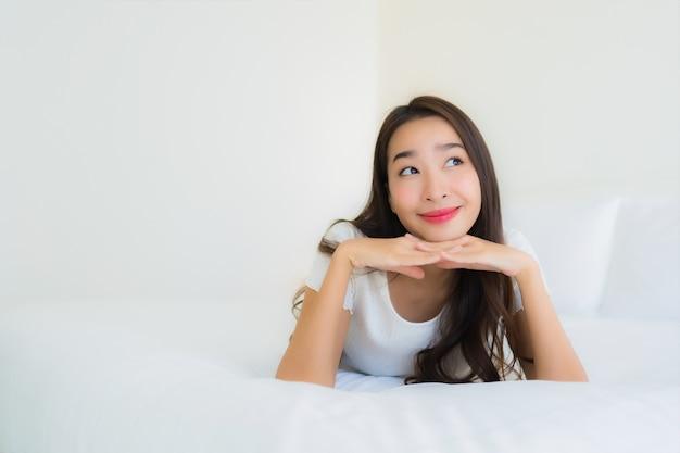 O retrato a mulher asiática nova bonita relaxa o sorriso feliz na cama com o cobertor branco do travesseiro