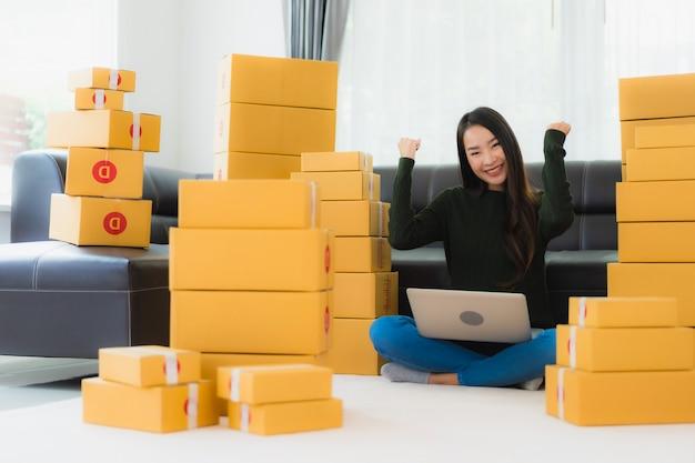 O retrato a mulher asiática nova bonita trabalha em casa e pronto para enviar