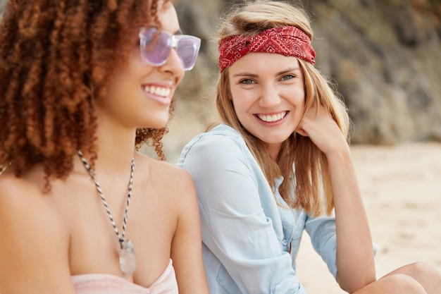 O retrato ao ar livre de uma mulher loira alegre usa bandana e camisa casual, senta-se perto de sua namorada afro-americana, tomam banho de sol juntos na praia, aproveite as condições do clima quente e ensolarado. casal de lésbicas