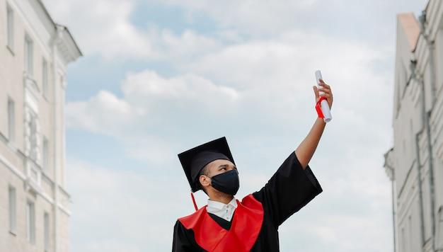 O retrato ao ar livre do estudante happy grad black, ele está em um mortarboard preto com borla vermelha e uma máscara facial no vestido mostra e olhando para o diploma na mão