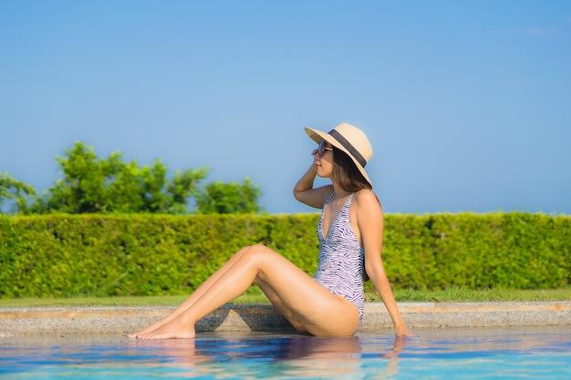 O retrato as mulheres asiáticas novas bonitas sorri feliz relaxa a piscina ao ar livre no recurso