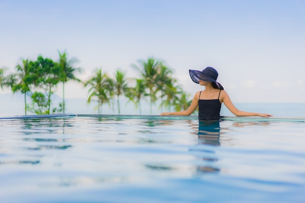 O retrato as mulheres asiáticas novas bonitas sorri feliz relaxa a piscina exterior no hotel