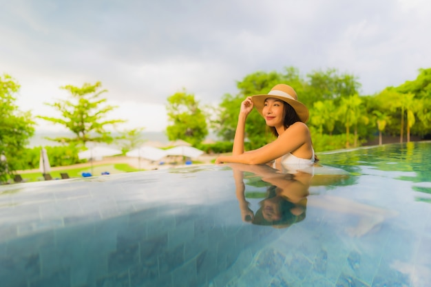 O retrato as mulheres asiáticas novas bonitas sorri feliz relaxa em torno da piscina exterior no hotel
