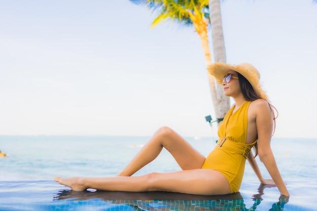 O retrato as mulheres asiáticas novas bonitas sorri feliz relaxa em torno da piscina exterior