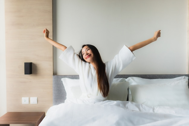 O retrato as mulheres asiáticas novas bonitas sorri feliz relaxa na cama