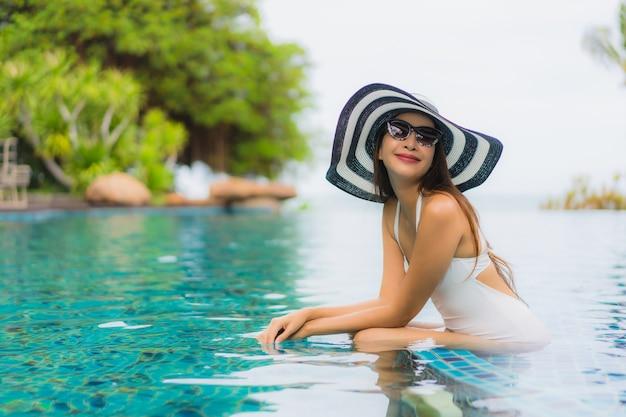 O retrato asiático novo bonito da mulher sorri feliz relaxa em torno da piscina no hotel resort
