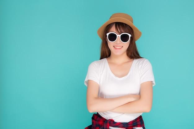 O retrato asiático novo do desgaste de mulher do retrato bonito e a expressão de sorriso dos óculos de sol seguros apreciam o verão nas férias isoladas no fundo azul.