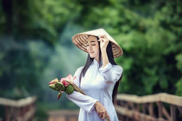 O retrato bonito de meninas asiáticas com a mulher tradicional do traje do vestido de ao-dai vietname, anda a ponte com lotus, em vietname.