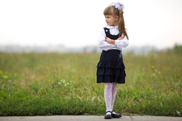 O retrato completo da menina bonito adorável pensativa séria da primeira série no uniforme escolar e no branco curva-se no cabelo louro longo na luz borrada - grama ensolarada verde e céu branco copia o fundo do espaço.
