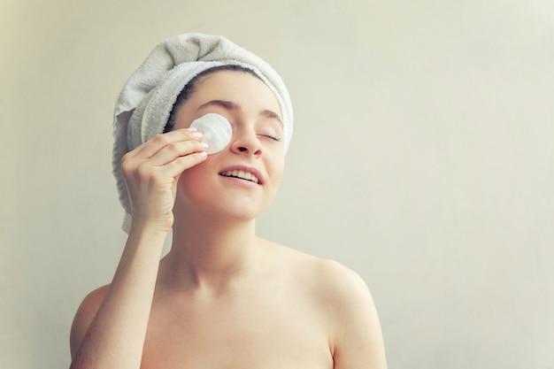 O retrato da beleza da mulher de sorriso na toalha na cabeça com a remoção saudável macia da pele compõe com a almofada de algodão isolada no branco. spa de limpeza de pele relaxar conceito