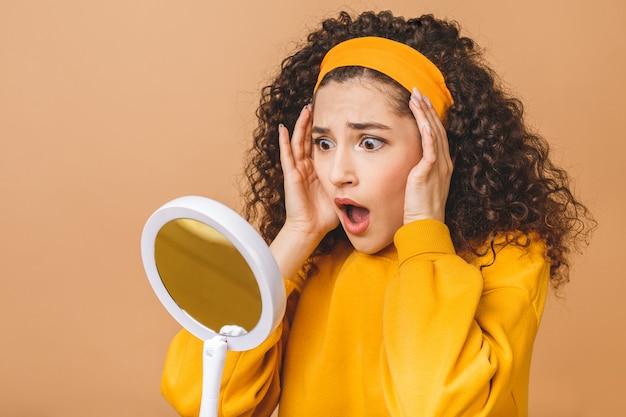 O retrato da beleza de uma mulher encaracolado atrativa surpreendida chocada surpreendida que examina sua cara ao guardar um espelho isolado sobre o fundo bege.