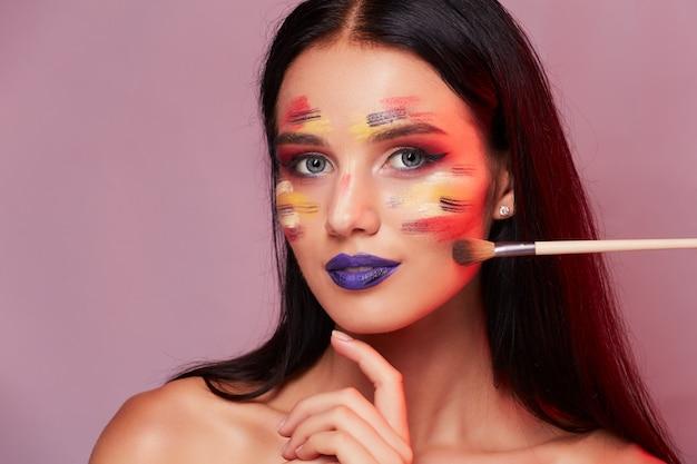 O retrato da beleza do close up de uma menina com compõe a arte e a escova. conceito de maquiagem.