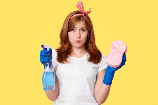 O retrato da dona de casa infeliz prende a garrafa com o detergente e a esponja, vestida ocasionalmente, limpa a casa, levanta no amarelo. empregada mulher descontente se sente cansado após a limpeza da primavera