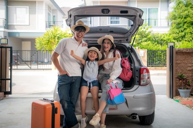 O retrato da família asiática com pai, mãe e filha parece feliz enquanto prepara a mala em um carro para férias.