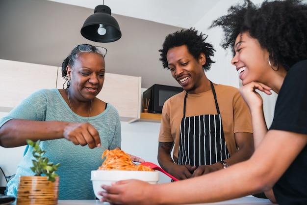 O retrato da família cozinha junto em casa.