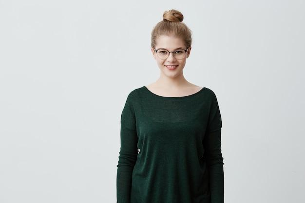O retrato da fêmea de sorriso contente que veste vidros e a camisola verde frouxa, está contra a parede cinzenta em branco, tem o bom humor após ter terminado o dia útil. menina loira europeia, regozijando-se sua vida