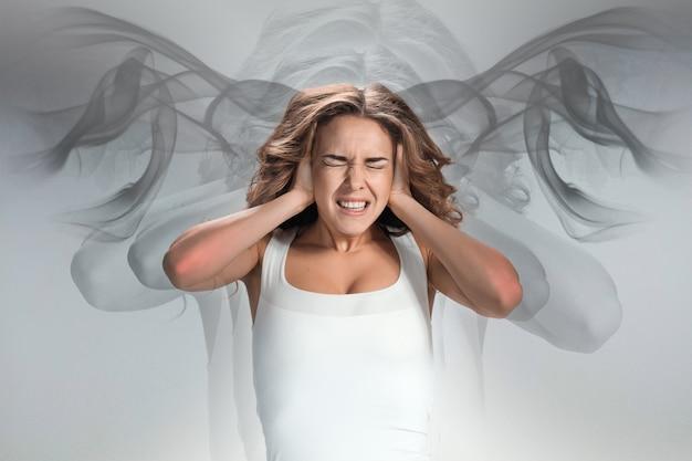 O retrato da jovem com emoções de dor em fundo cinza. dor de cabeça de conceito