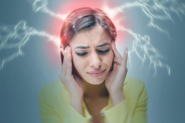 O retrato da jovem com emoções de dor em fundo cinza. dor de cabeça do conceito. imagem borrada
