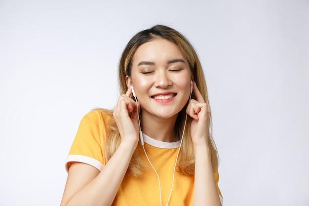 O retrato da jovem mulher asiática feliz escuta a música com fones de ouvido.