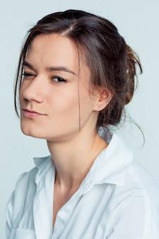 O retrato da jovem mulher com emoções pensativas no espaço azul