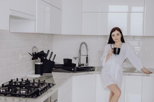 O retrato da jovem mulher na veste branca após o banho mantém um copo com café ou chá contra a parede da cozinha. feche o rosto sorriso.