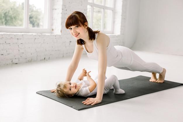 O retrato da mãe nova bonita nos esportes brancos veste-se com seu bebê pequeno encantador que faz exercícios no tapete preto