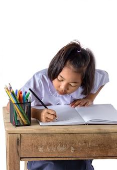 O retrato da menina asiática na farda da escola está tirando com os lápis da cor isolados no fundo branco
