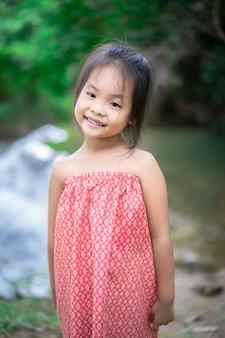 O retrato da menina asiática prepara-se para jogar na água da natureza no feriado