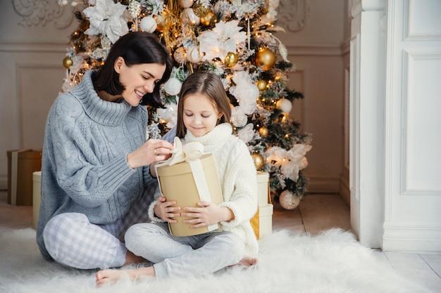 O retrato da menina bonita e da mãe fêmea bonita sentam-se junto no tapete quente, mantenha a caixa atual, aprecie a árvore decorada do ano novo. família passar um tempo juntos. celebração e conceito de férias