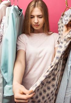 O retrato da menina bonita escolhe o vestido, menina dentro de seu guarda-roupa isolado