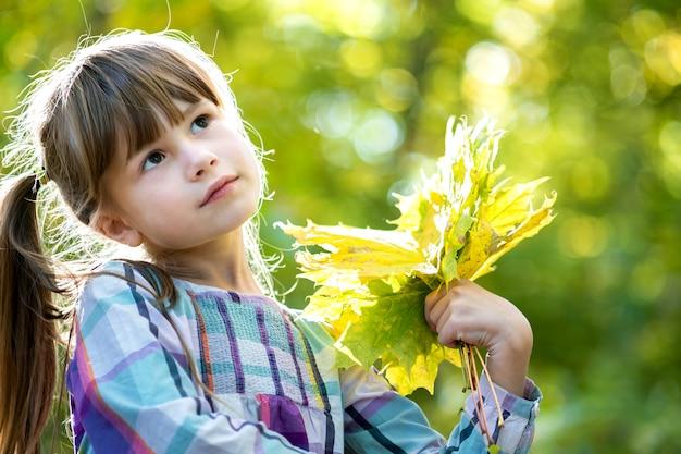 O retrato da menina bonita feliz da criança que guarda um grupo da árvore caída sae na floresta do outono. garoto feminino positivo, aproveitando o dia quente no parque outono.