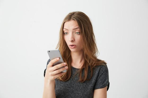 O retrato da menina bonita nova surpreendida que olha a tela do telefone com a boca aberta que surfa wed o internet.