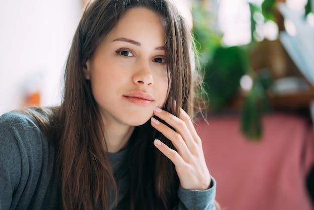O retrato da menina bonito de sorriso do moderno que olha fixamente na câmera ao escrever exercícios da faculdade no caderno.