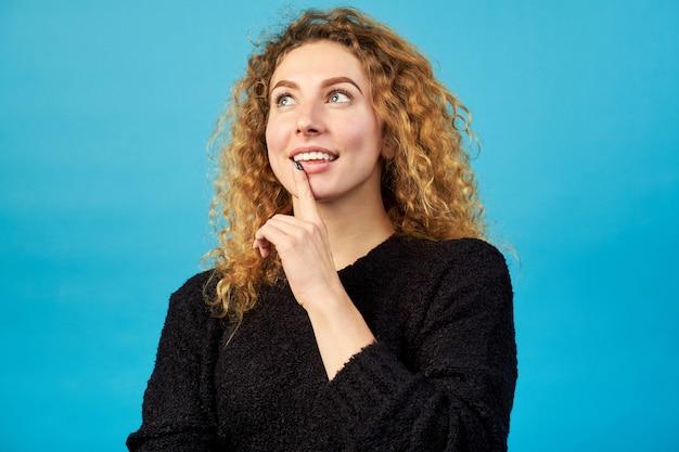 O retrato da menina encaracolado ruiva atrativa de sorriso alegre pensativa vestiu a camisola preta e o pensamento sobre algo ou alguém.