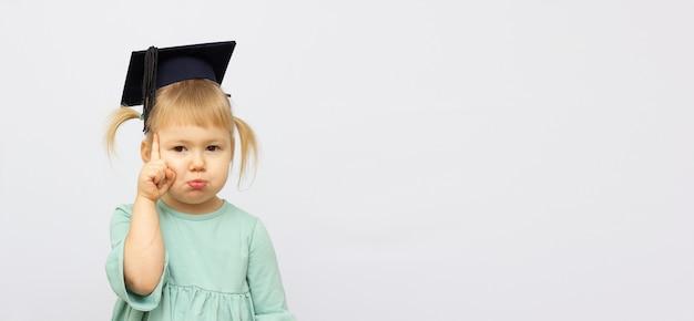 O retrato da menina está usando um chapéu de pós-graduação e sorri de felicidade com espaço de cópia para o banner do conceito de educação