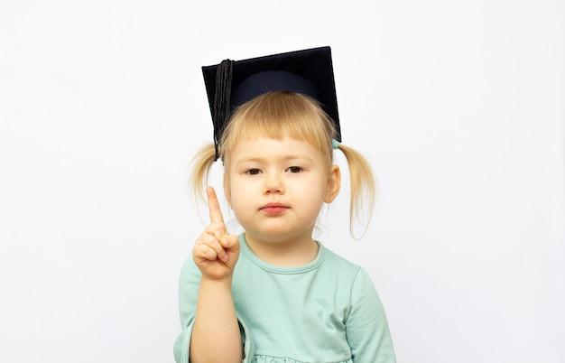 O retrato da menina está usando um chapéu de pós-graduação e sorri de felicidade para o conceito de educação
