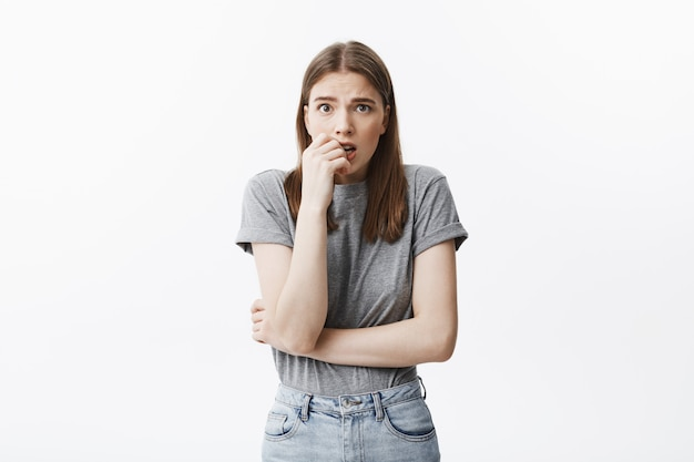O retrato da menina infeliz bonita jovem estudante europeu com cabelos escuros e olhos castanhos em roupas da moda roe os dedos, com expressão assustada, preocupado com ela engravidar.